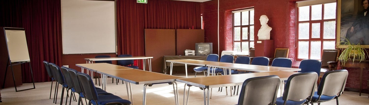 Meeting room with bust, tables, several chairs and a whiteboard