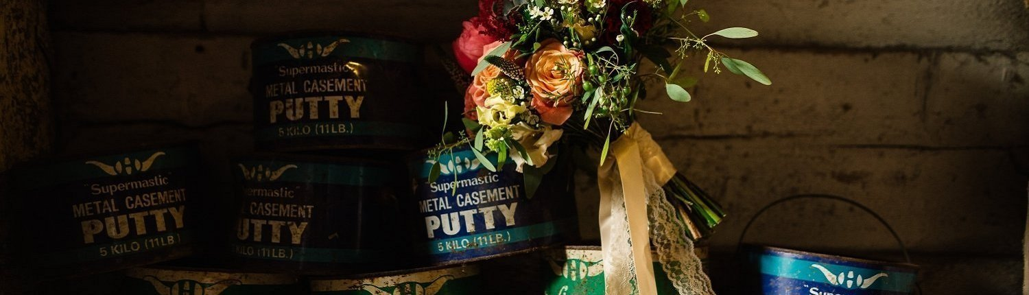 Wedding bouquet in front of several cans of metal casement putty