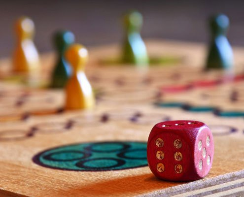 A close up of a wooden board game and dice