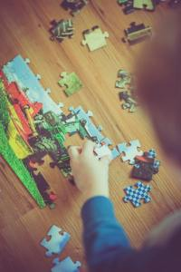boy putting puzzle together kids staying home