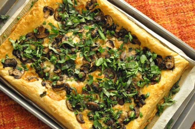 tray of mushroom and taleggio puff pastry on an orange back drop