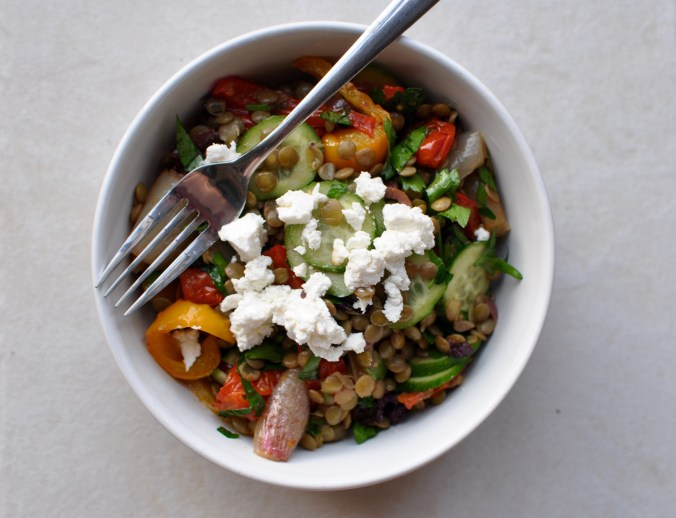 Bowl of lentil salad with crumbled feta and roasted vegetables