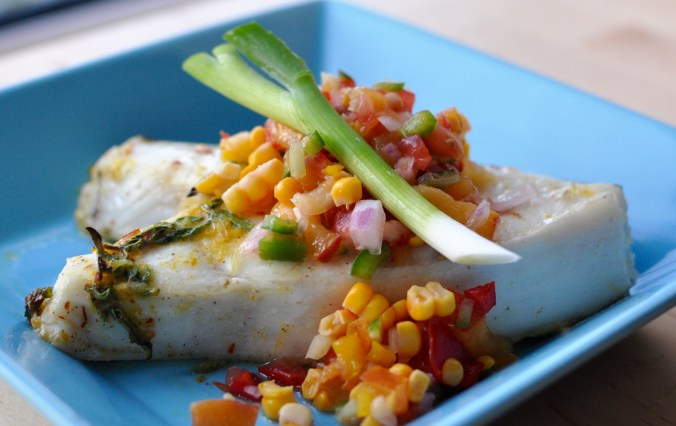 A blue plate with a halibut steak and fresh fruit salsa.