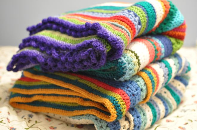Stack of colourful crochet blankets.