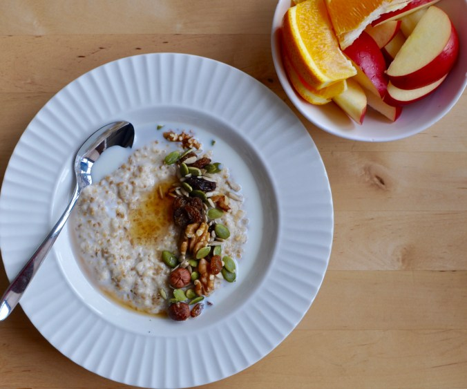 A shallow bowl full of steel cut oats, nuts, seeds, and brown sugar beside a bowl of orange sections and apple slices.