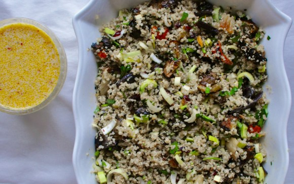 White dish full of quinoa and roasted vegetable salad beside a glass container containing creamy orange salad dressing.