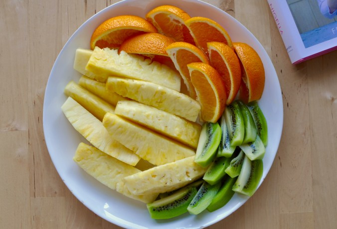 Shallow plate of fruit containing pineapple, oranges, and kiwi.