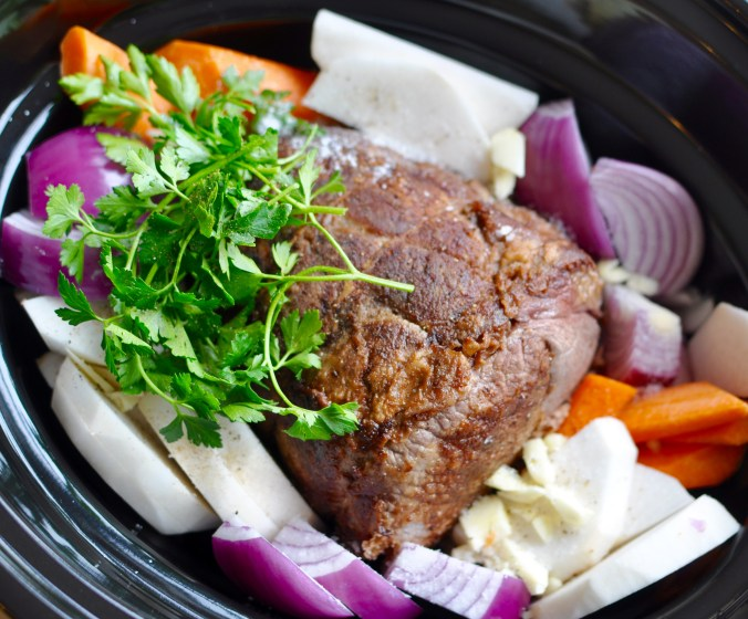 Pot roast and vegetables in a black slow cooker before cooking.