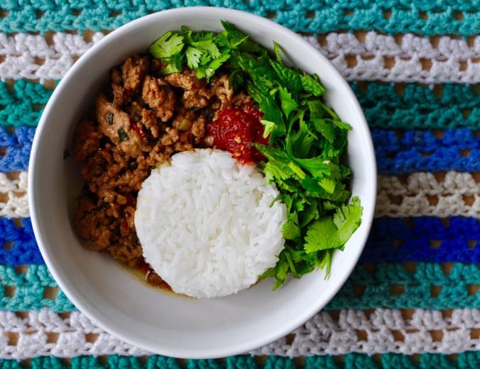 Round white bowl with white rice, minced pork, chili sauce, and fresh herbs.