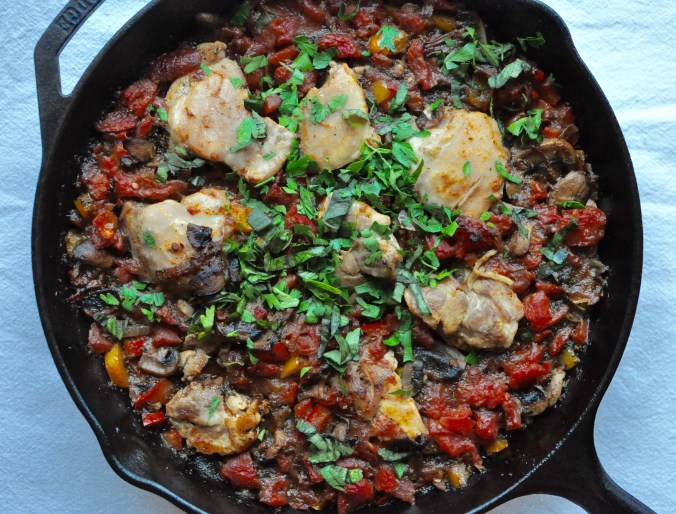 Large cast iron skillet full of chicken cacciatore sprinkled with fresh herbs on a blue tablecloth.