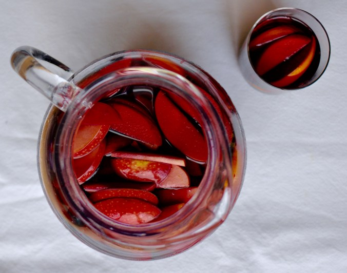 Classic red wine sangria in a clear glass pitcher that is filled with sliced apples and oranges. Laid out on a white tablecloth with a glass of sangria to the side.