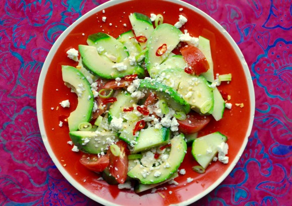 An orange plate full of cucumber, tomato, and avocado salad on a bright pink and blue tablecloth. The salad is garnished with chilies, feta cheese, and scallions.