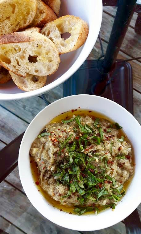 A white round bowl full of creamy eggplant dip, garnished with fresh basil and mint beside a bowl of grilled baguette slices.