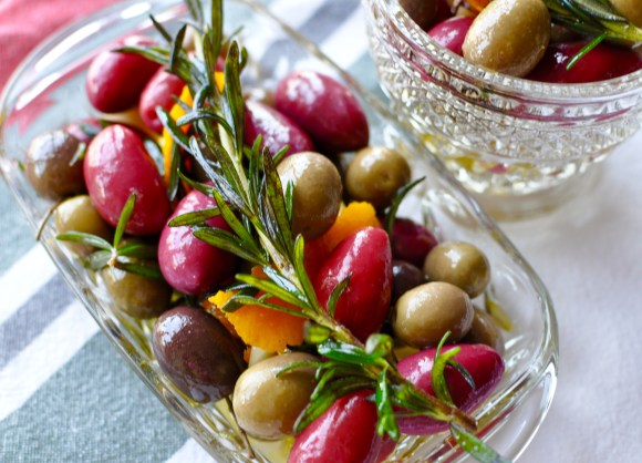 Clear glass dish with marinated olives with orange and rosemary on a white, green, and red striped tablecloth.