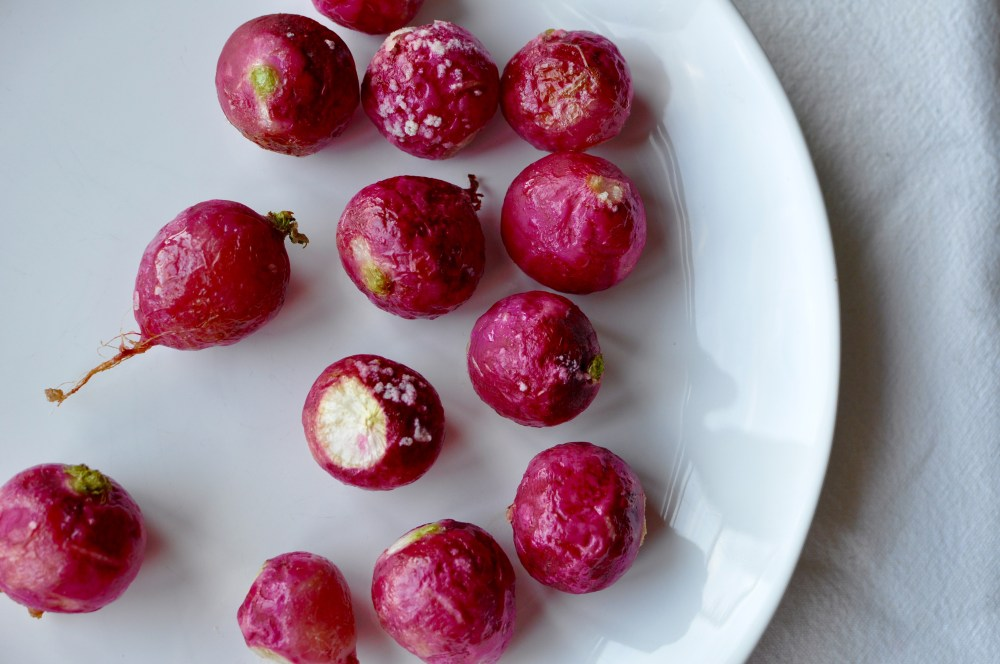 Roasted pink radishes on a white plate.
