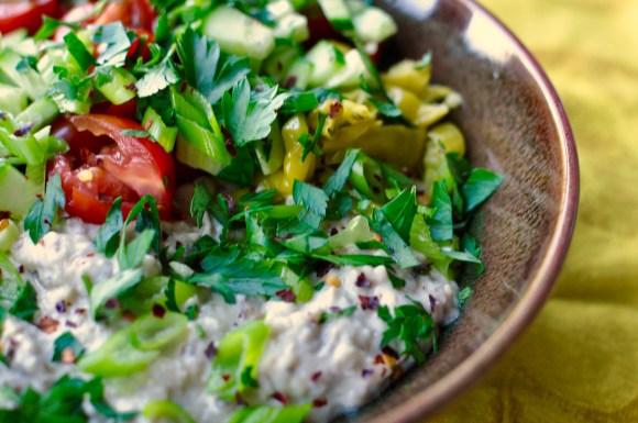 Brown shallow earthenware bowl filled with eggplant dip and with a topping of fattoush salad