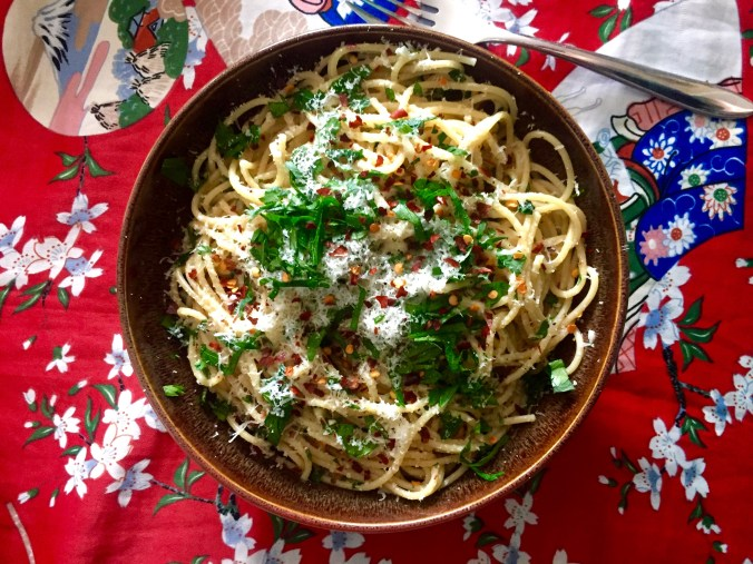Spaghetti with Fresh Herbs, Chilies, Parmesan, and Black Pepper on a vivid red background.