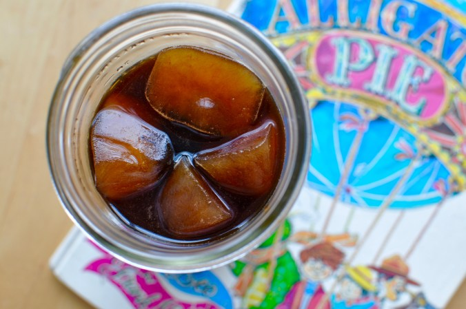 A Mason jar filled with iced coffee and coffee ice cubes sitting on the book Alligator Pie by Dennis Leery.