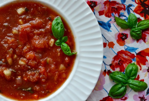 A shallow white soup bowl full of watermelon gazpacho with roasted apricots, tomatoes, and red onions on a red, white, blue floral background. Small fresh basil clusters are arranged on the gazpacho and background.