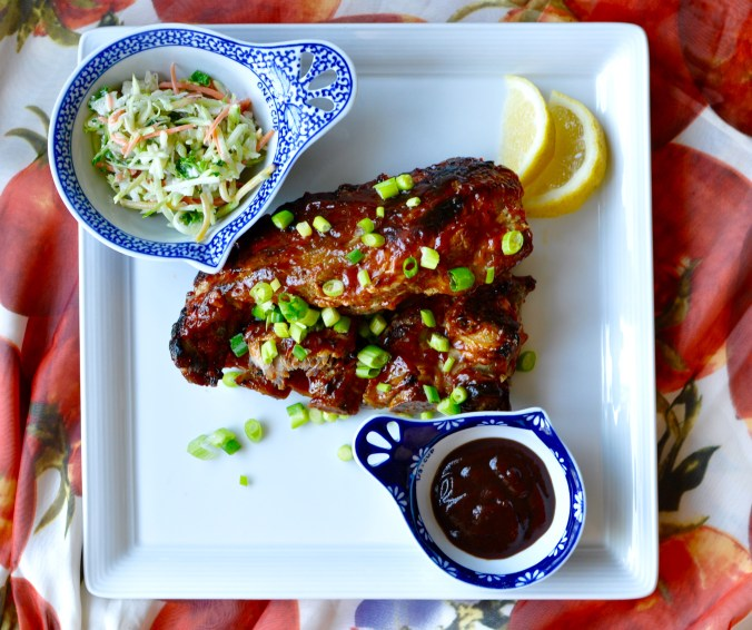 Ribs with scallions, coleslaw, and barbecue sauce in small dishes on a rectangular plate.