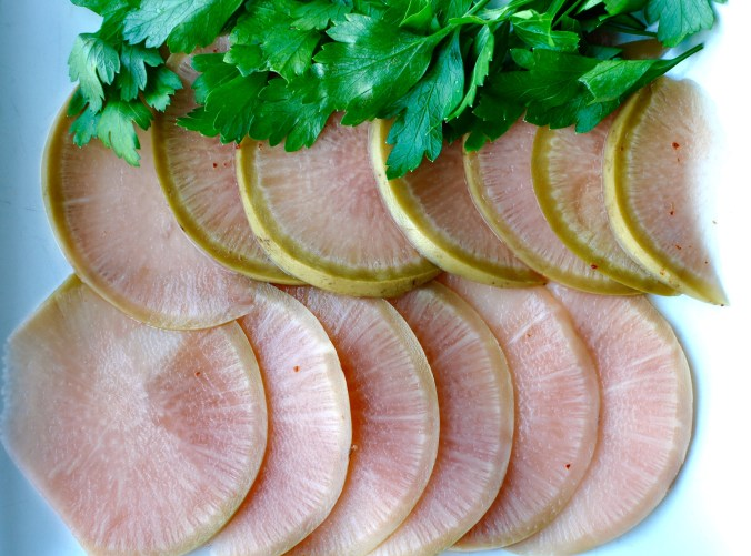 Thinly sliced watermelon radish on a white background with parsley.