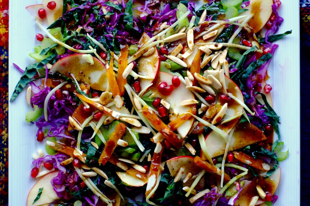 Big crunchy winter salad on a square white plate with maple dressing.