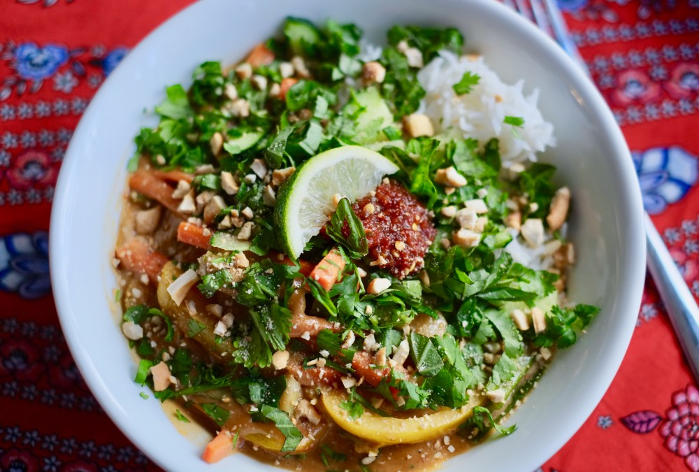 White bowl on an orange and blue-flowered tablecloth full of vegetable stir fry topped with cashew butter sauce, chopped fresh basil and cilantro, sambal oelek, and crushed cashews.