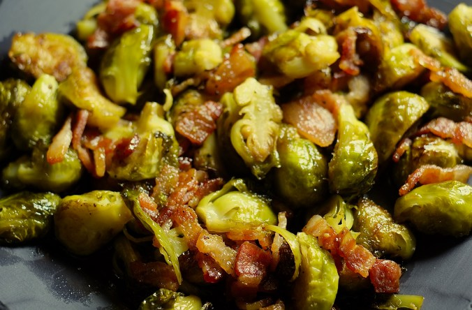 Slate serving dish piled high with pan seared maple Brussels sprouts and bacon.