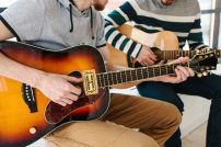 A student taking a guitar lesson with a teacher