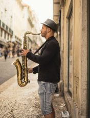 Man playing saxophone on the street after taking a saxophone lesson.