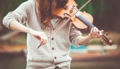 Woman plats violin outside after taking violin lessons