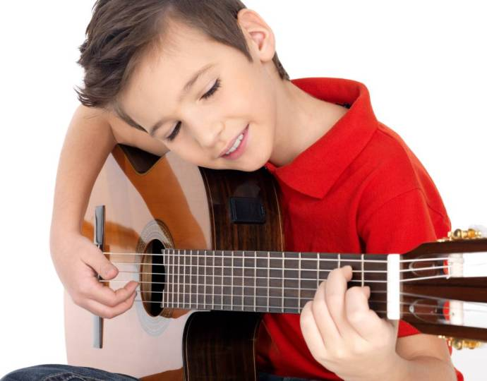 Best Guitar Books for Beginners with a kid practising classical guitar