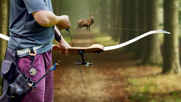 A bow Hunter aiming at a White tail buck against