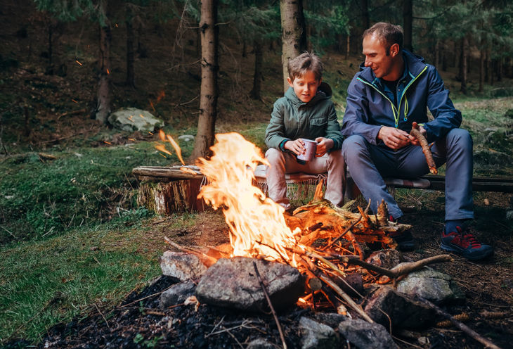 Father with son warm near campfire