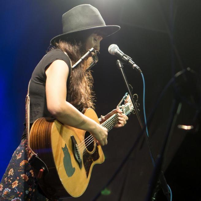 Sissi van Thal mit Hut, Mundharmonika und Gitarre.