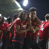 LEIGH, GREATER MANCHESTER - DECEMBER 17:  D'Mani Bughail-Mellor and Mason Greenwood of Manchester United U18s celebrate Di'shon Bernard scoring their third goal during the FA Youth Cup Third Round match between Manchester United U18s and Chelsea U18s at Leigh Sports Village on December 17, 2018 in Leigh, Greater Manchester.  (Photo by Matthew Peters/Manchester United via Getty Images)