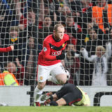 MANCHESTER, ENGLAND - MARCH 10: Wayne Rooney of Manchester United celebrates scoring their first goal during the UEFA Champions League First Knockout Round Second Leg match between Manchester United and AC Milan at Old Trafford on March 10 2010 in Manchester, England. (Photo by Tom Purslow/Manchester United via Getty Images)