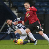 WEST BROMWICH, ENGLAND - FEBRUARY 14: Luke Shaw of Manchester United in action with Robert Snodgrass of West Bromwich Albion during the Premier League match between West Bromwich Albion and Manchester United at The Hawthorns on February 14, 2021 in West Bromwich, England. Sporting stadiums around the UK remain under strict restrictions due to the Coronavirus Pandemic as Government social distancing laws prohibit fans inside venues resulting in games being played behind closed doors. (Photo by Matthew Peters/Manchester United via Getty Images)