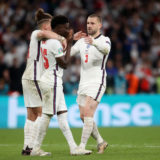 LONDON, ENGLAND - JULY 11: Bukayo Saka of England is consoled by teammates Kalvin Phillips and Luke Shaw after having their team's fifth penalty saved in a penalty shoot out during the UEFA Euro 2020 Championship Final between Italy and England at Wembley Stadium on July 11, 2021 in London, England. (Photo by Carl Recine - Pool/Getty Images)