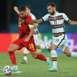 SEVILLE, SPAIN - JUNE 27: Eden Hazard of Belgium makes a pass as he is tackled by Bruno Fernandes of Portugal during the UEFA Euro 2020 Championship Round of 16 match between Belgium and Portugal at Estadio La Cartuja on June 27, 2021 in Seville, Spain. (Photo by Alexander Hassenstein/Getty Images)