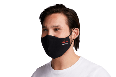 Photograph of a man wearing a HeiQ Viroblock +Multi Hi-Tech Protective Washable and Reusable Black Face Mask. HeiQ Face Mask has the words HeiQ Viroblock + Multi Hi-Tech written on one side of the mask, and a tag which says Swiss Tech Inside on the other side of the mask.