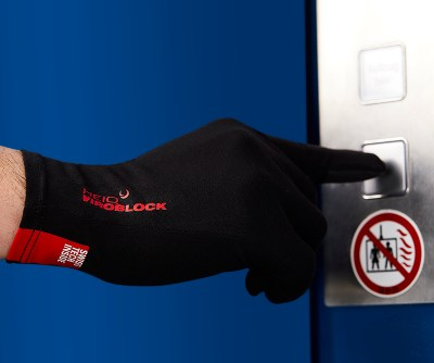 Photograph of a hand wearing the HeiQ Viroblock Antimicrobial black gloves, and pressing a button in a lift. The words HeiQ Viroblock are written small in red on the back of the glove. There is a red tag on the wrist of the glove that says, Swiss Tech Inside