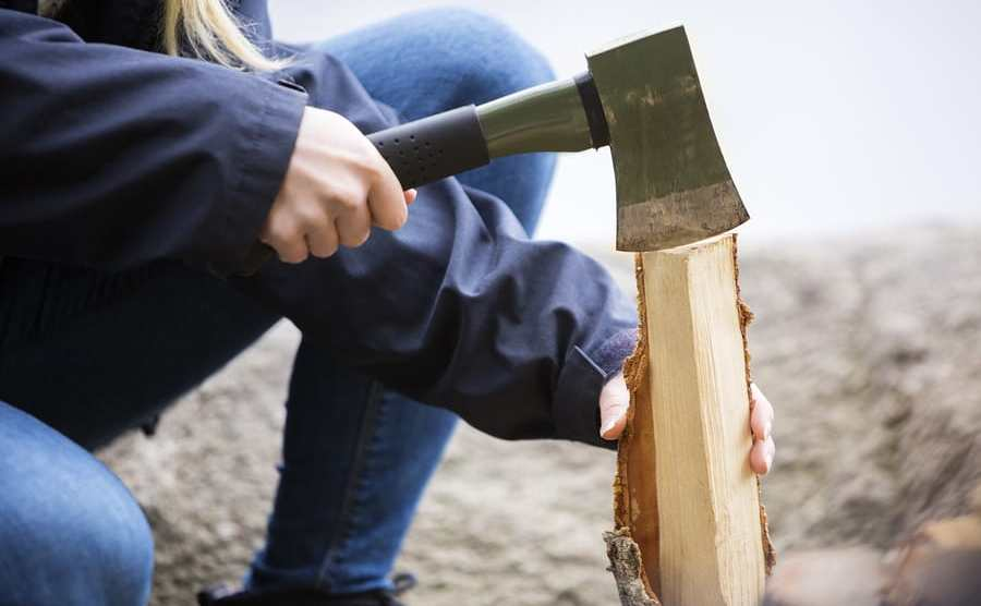 Woman Cutting Wood For Bonfire On Campsite