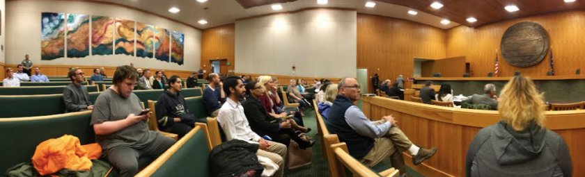 Photo of people sitting in a courtroom waiting for the oral arguments.