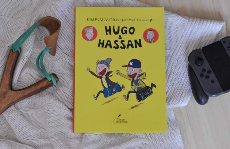 Als Hugo und Hassan an einem öden Nachmittag zum ersten Mal im Hinterhof aufeinandertreffen, stehen sie erst einmal wie zwei Cowboys gegenüber und vermöbeln sich fast. Trotzdem sind sie ab sofort fast unzertrennlich. Denn Hugo und Hassan sind auf einer Wellenlinie. Sie lieben Fußball, Computerspiele und Arschbomben im Schwimmbad. #comic #freundschaft #jungs #zocken #fußball #kloppen #streit #freunde #lesen #kidnerbuch