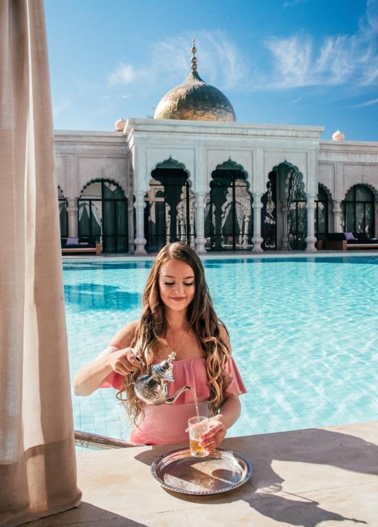 Millainen matkailija olen | Tyttö kaataa teetä palatsissa uima-altaan äärellä.