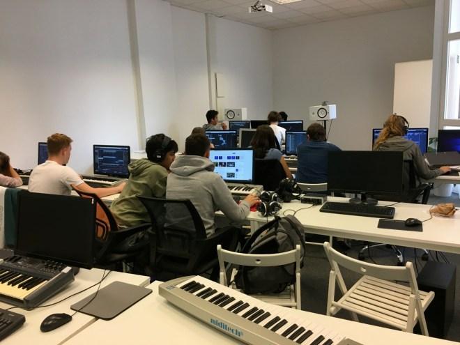 Man sieht die Schüler an ihren Computern arbeiten
