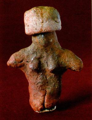 Грубо изработена фигура на седната жена, со капа на главата во вид на шубара