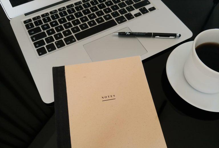 Zdjęcie: komputer, notes, filiżanka kawy leżące na czarnym stole