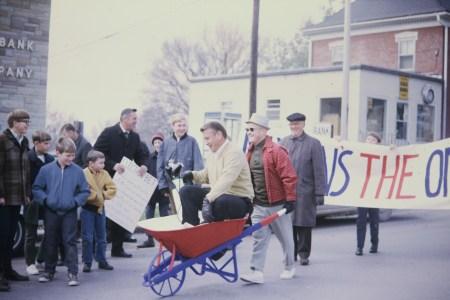 Photo of Paul Scott pushing Doc Sautter in wheelbarrowr